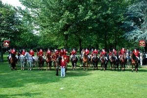 Berittener Fanfarenzug auf Pferden in roter Uniform